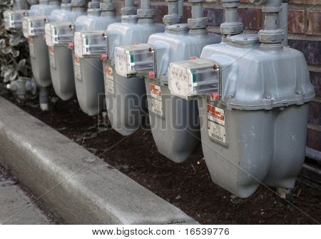 Row gray gas meters at an apartment complex done with a narrow field of focus without manifold