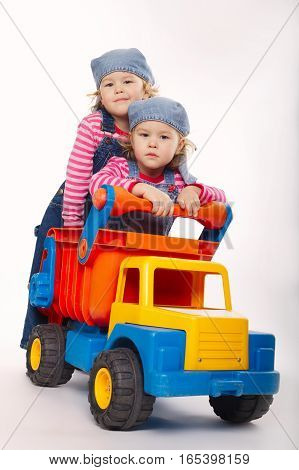 two funny twins girls with toy car on white