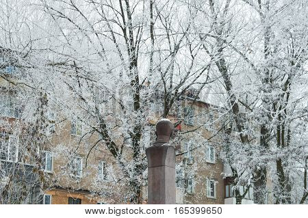 A view of the multi-storey building in the park an unknown monument in the foreground winter frost on branches