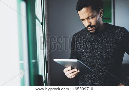 Selective focus. Pensive bearded African man using digital tablet while standing near the window in his modern apartment. Concept of young business people working at home. Blurred background.