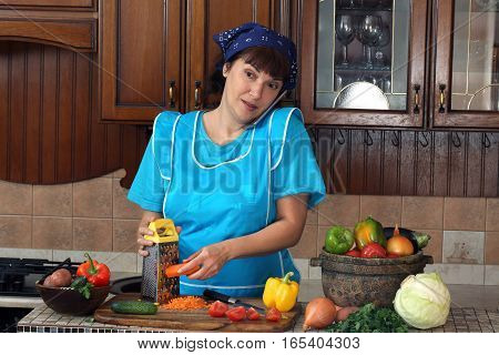 woman talking on the phone and rubs carrots on a grater