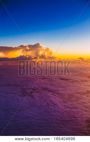 Amazing beautiful sunset sunrise over mountains from height of airplane, plane. Bright Blue, Orange, Yellow and Purple Colors of Sunrise Sky Background.