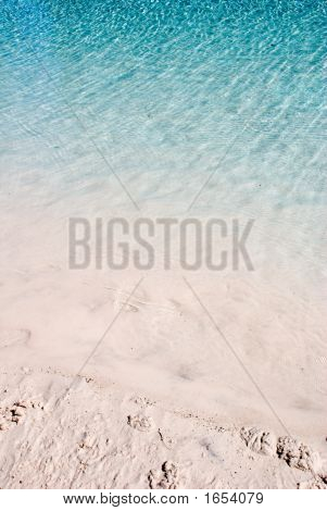 Blue Water Ripples On White Sandy Beach