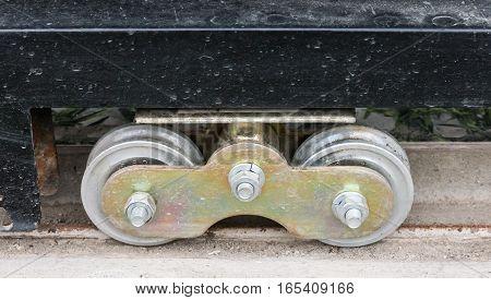 New metal wheel of the metal gate on the rusty rail