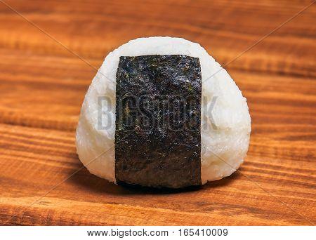 Japanese rice ball onigiri on wooden background.