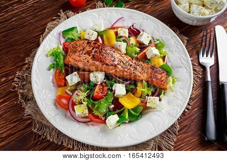 Fried Salmon steak with fresh vegetables salad, feta cheese. concept healthy food