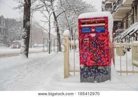 Montreal QC Canada - 29 december 2016: Red Canada Post mailbox on the street during snowstorm