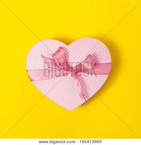 Beautiful elegant Present Gift in Heart Shape on Yellow colorful Background. Top view. Spring Concept or Mother's Day Concept.