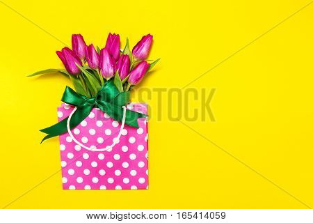Fresh beautiful lila tulips in gift package on bright yellow background. Spring concept. Top view with Copy Space.