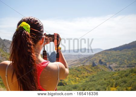 Young girl photographed in summer mountain landscape
