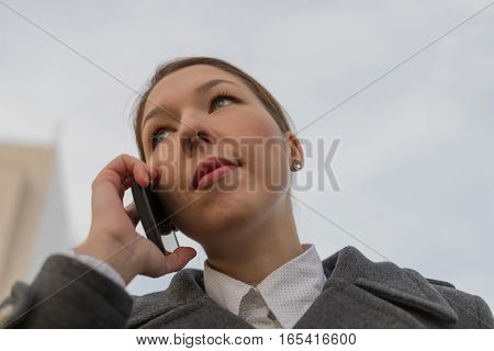 Successful Business Woman Talking On Cellphone While Walking Outdoor