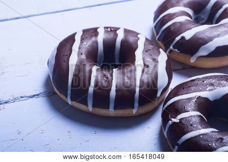 assorted donuts with chocolate frosted pink glazed and sprinkles donuts.