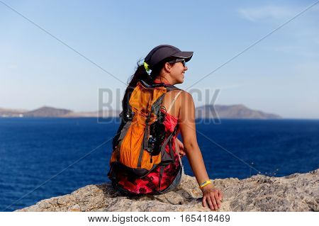 Brunette back sits on mountain on background of sea