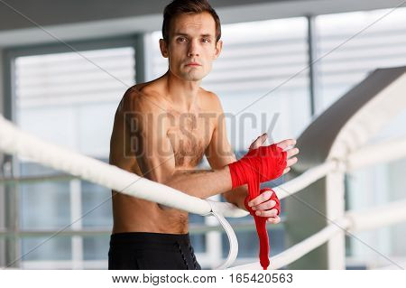 Athlete closeup near boxing ring with boxing bandages