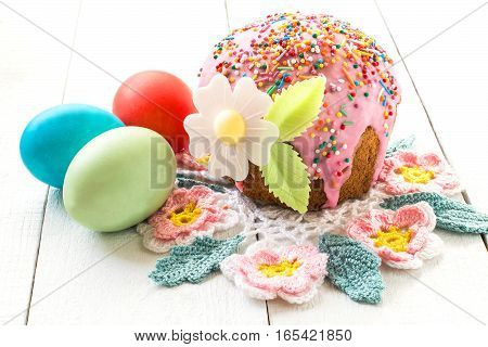 Traditional Easter treats: Easter cake and colorful easter eggs on a white table