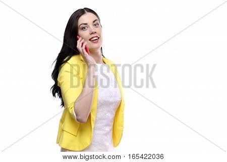 Pretty young woman in yellow clothes enjoying a conversation on cellphone on white.