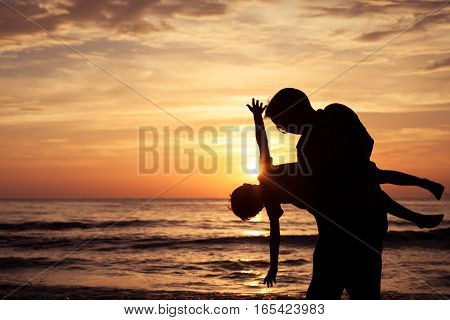 Father and son playing in the park at the sunset time. People having fun on the beach. Concept of friendly family and of summer vacation.