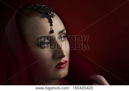 Eastern woman portrait photo. Beautiful eastern woman in red head shawl portrait photo.