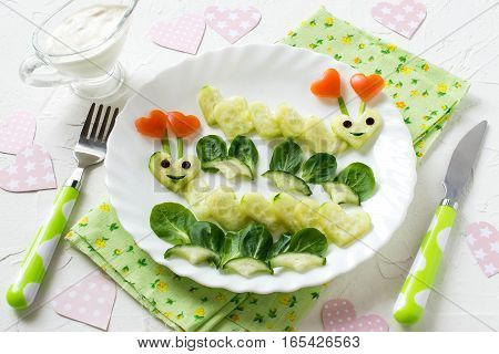 Creative idea of food decoration for Valentines Day. Fun loving caterpillars carved in the shape of hearts of cucumber. Healthy and vegetarian food. Symbols of Valentines Day in the design