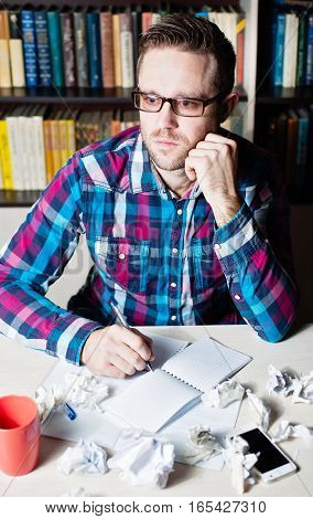 Young Man Working And Thinking In The Workplace