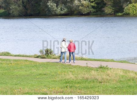 Two mature women walking near river and looking on water