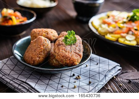 Vegetarian Fritters Made Of Buckwheat, Bean, Leek, Garnished With Potato And Steamed Vegetble