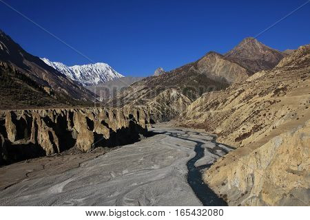 Landscape near Manang Annapurna Conservation Area Nepal. Marsyangdi river limestone cliffs and snow capped Tilicho Peak.