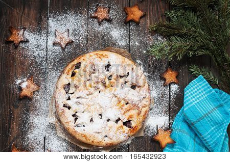 Cherry pie and cookie on rustic wooden background.
