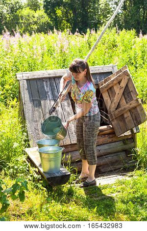 Young attractive woman near the village wooden water well in summer sunny day