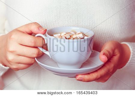 Young woman wrapped in a white knitted blanket and holding mug with hot coffee or cocoa and marshmallows. Female hands holding green cup of hot cocoa. Christmas morning. New Year. Cozy winter.