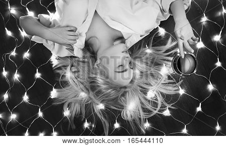 beautiful girl lying on floor with christmas lights, monochrome
