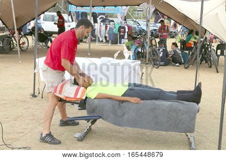 Chiropractor Assisting Cyclist At Finish Line At The Mathaithai Mountain Bike Race
