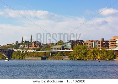 Georgetown waterfront suburb in Washington DC with a view on university historic buildings. Potomac River near Key Bridge with kayaks and motorboats.