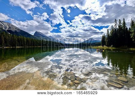 Friends in a boat on the beautiful clear lake with reflections of clouds. Honeymoon lake in Canadian Rocky Mountains. Jasper National Park. Alberta. Canada.