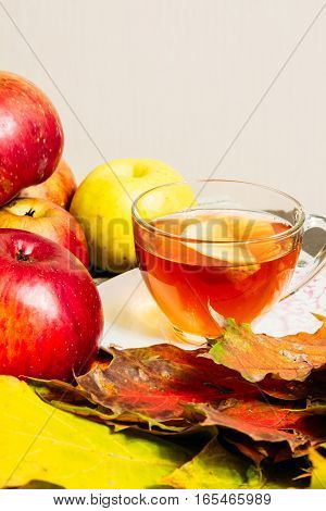 Apples And Maple Leaves On The Table Next To A Cup Of Tea