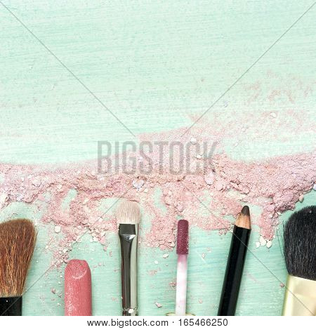 Makeup brushes and lipstick on a teal blue background, with traces of powder and blush on it. A square template for a makeup artist's business card or flyer design. With plenty of copyspace
