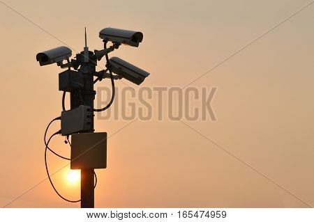Silhouette of surveillance cameras or circuit cameras in evening day with copy space for text.