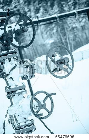 Wellhead valve. Oil and gas concept. Industrial site during winter period. Toned.