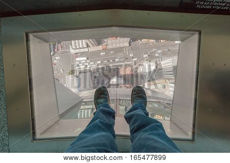 Auckland New Zealand- December 12 2013. A man step on traveling glass's floor of NZ sky tower and looking down New Zealand city.