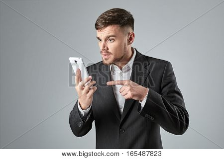 Portrait of a handsome businessman making a phone call against a grey background. Emotions