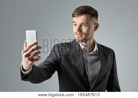 Businessman in a black suit makes the selfie on the smartphone against a grey background. Emotions