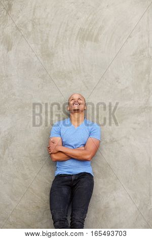 Smiling African Man Leaning Against Wall And Looking Up