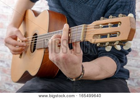 Close-up view of man's hand playing the acoustic guitar