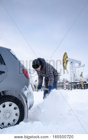 Man shoveling snow to free stuck car. Winter period. Industrial site and pump jack background.