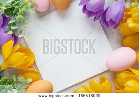 Easter card with blank white sheet surrounded by frame of yellow and purple crocus flowers and colorful Easter eggs