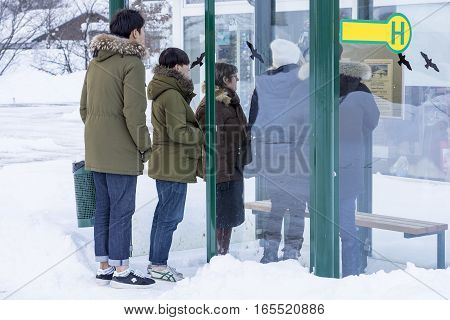OBERTRAUN, AUSTRIA - JANUARY 10, 2017 : Group of People Waiting at Bus Stop and Looking at the Timetable in Cold Snowy Winter Day
