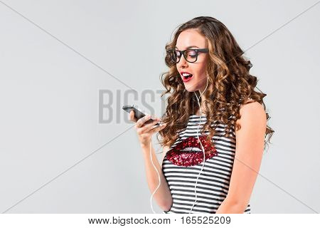 Happy young woman listening music with headphones. Isolated portrait on gray studio background