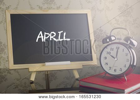 APRIL on chalkboard with alarm clock and flare