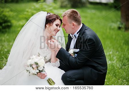 Wedding Couple Sitting On Green Grass And Looking Each Other.