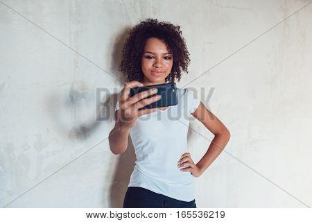 Beautiful smiling african girl make selfie on grey background